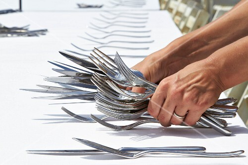 A table being laid with cutlery for a wedding reception
