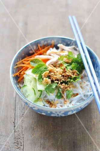 Rice noodles with chicken, vegetables, herbs and roasted onions