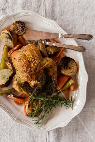Roast chicken with lemon, vegetables and herbs