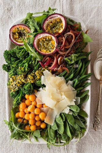 A large salad with green vegetables, marinated onions, passion fruit and Parmesan cheese