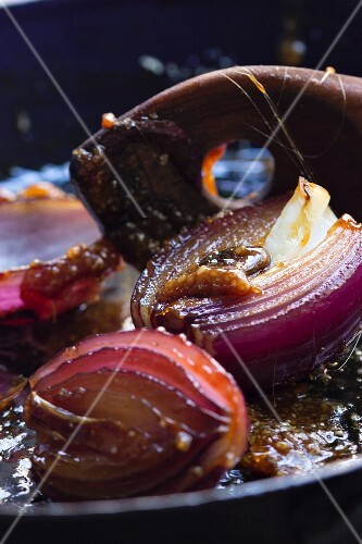 Caramelised red onions with a wooden spoon and caramel threads