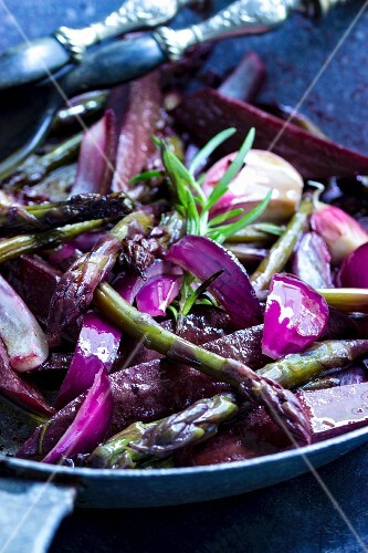Purple carrot salad with green asparagus, rosemary and red onions