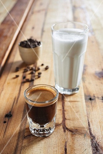 A glass of espresso and a glass of hot milk