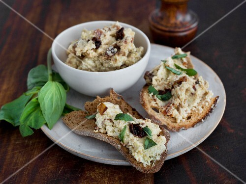 An artichoke dip in a bowl and on slices of bread