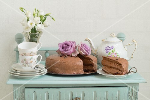 Chocolate cake with coffee crockery on a mint coloured sideboard