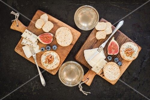Crackers, Brie, Danish caraway cheese, blue cheese, mini crostini, walnuts, fix, blueberries and Federweisser (a cloudy beverage in the process of fermenting, somewhere in between must and wine) on wooden boards