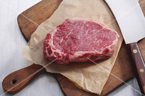 Raw lean entrecôte on a piece of paper on a chopping board (seen from above)