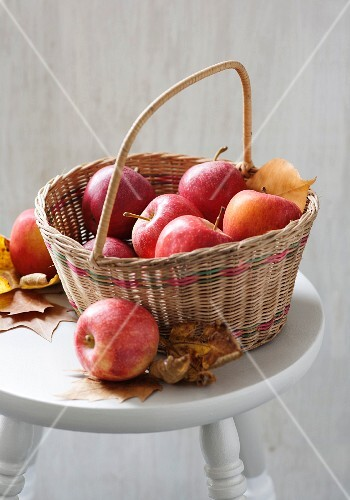 Apples in a basket with autumn leaves