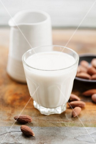 A glass of almond milk and almonds