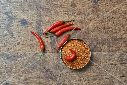 Chilli powder and fresh chillis on a wooden surface (seen from above)