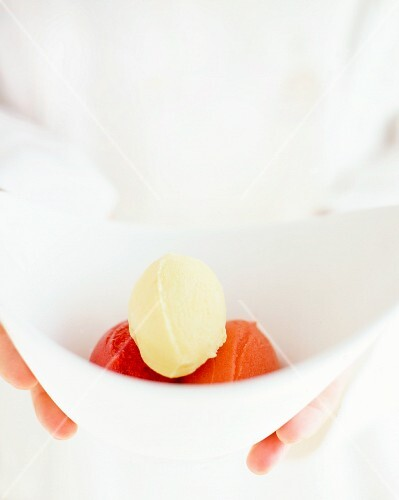 Hands holding a bowl of vanilla ice cream, blood orange sorbet and strawberry sorbet