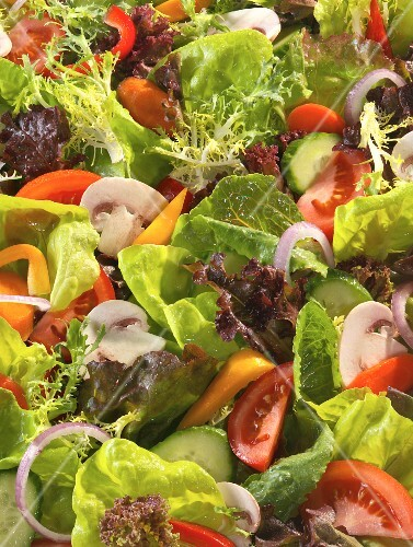 A green salad with mushrooms, onions and tomatoes