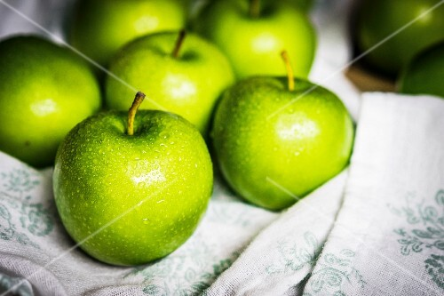 Freshly washed green apples on a tea towel