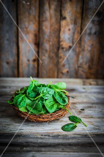 Fresh spinach in a basket on a rustic wooden surface