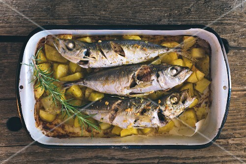 Roast mackerel with potatoes in a roasting dish