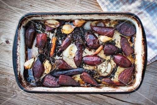 Oven-roasted vegetables in a roasting dish (beetroot, garlic, carrots, onions)