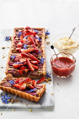 Rhubarb tart with fresh strawberries, borage flowers, mascarpone and strawberry and rhubarb coulis