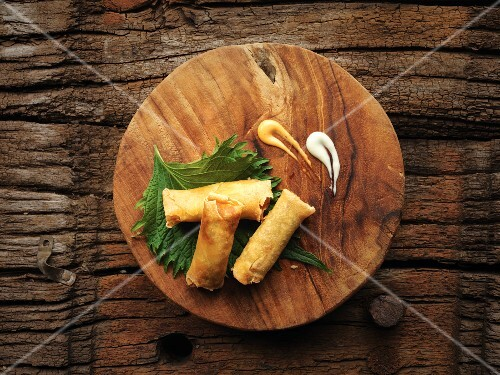 Spring rolls filled with prawns and vegetables on a shiso leaf