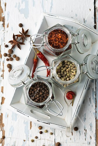 Various spices in storage jars on a tray