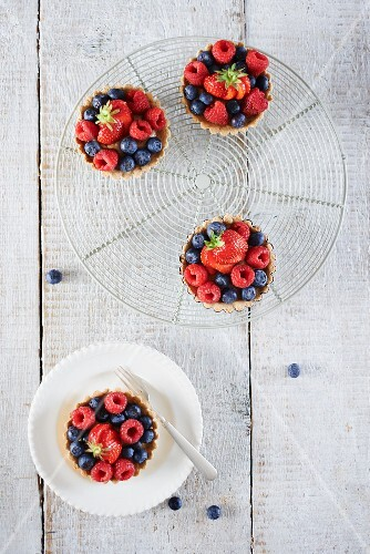 Berry tartlets on a cooling rack (seen from above)