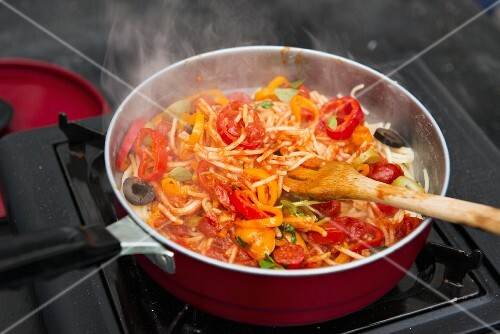 Spaghetti with peppers, tomatoes and olives in a pan