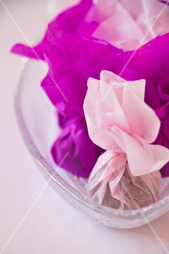 Schokoladenkonfekt in violettem und rosa Papier