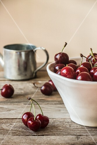 Cherries in a white ceramic bowl on a wooden table