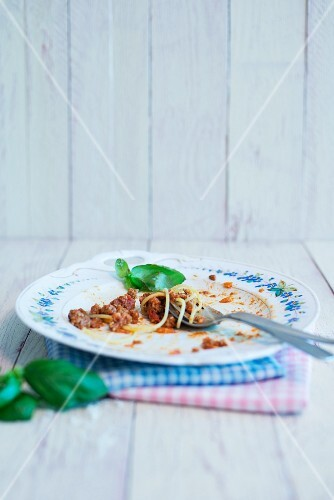 The remains of spaghetti Bolognese on a plate with a basil leaf
