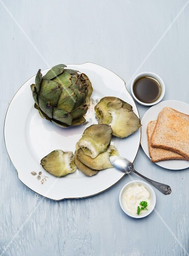 Cooked artichokes on a porcelain plate with aioli and vinaigrette