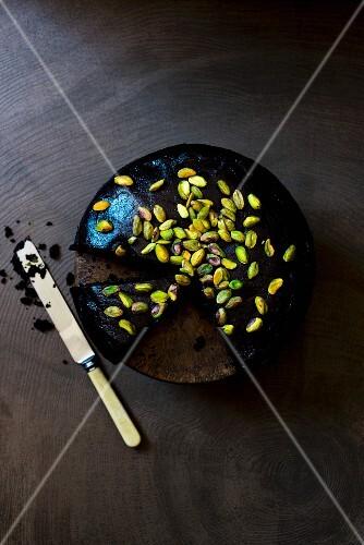 Vegan chocolate cake with pistachio nuts, sliced