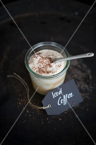 An iced coffee in a jar with a porcelain spoon and a paper label