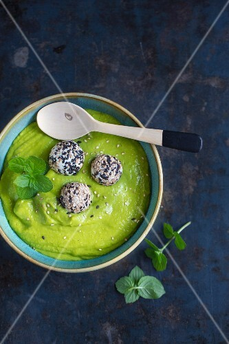Pea soup with mint leaves and feta cheese balls rolled in sesame seeds