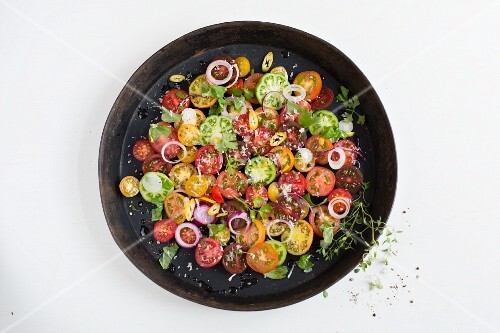 An heirloom tomato salad with onion rings and herbs