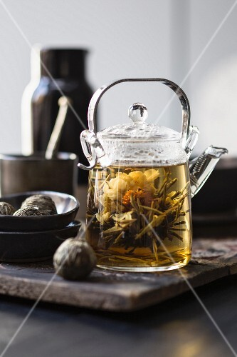 White tea in a glass teapot with a tea flower