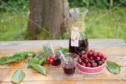 Carafe and glasses of juice and a bowl of cherries