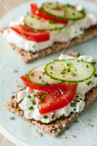 Crispbread topped with cottage cheese, tomatoes, cucumber and chives