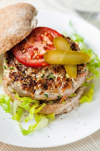 A pork burger with chillis, tomatoes and gherkins