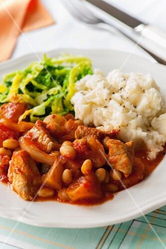 Slow cooked pork and bean stew with mashed potatoes