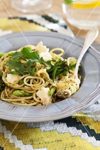 Spaghetti with herb pesto, broccoli, green asparagus, feta cheese and rocket