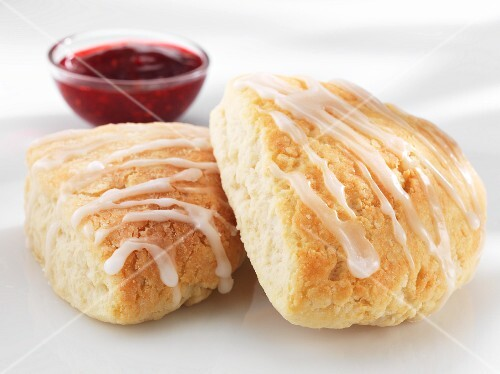 Scones with icing and raspberry jam