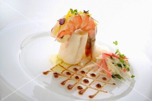A king prawn on bass fillet with a sauce grid and a vegetable salad