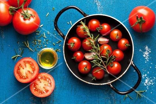 ingredients for pasta sauce: cherry tomatoes, rosemary, garlic and olive oil