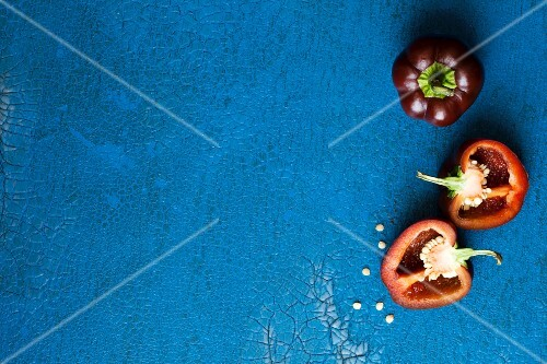 Dark red mini peppers, whole and halved, on a blue surface