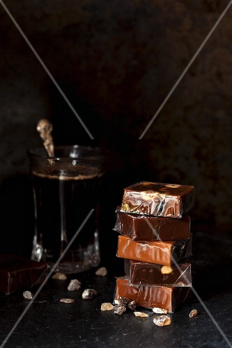 A stack of cellophane-wrapped caramel bonbons, next to a glass of coffee