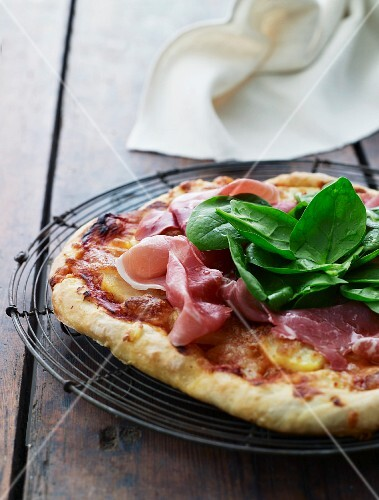 Pizza with potatoes, raw ham and spinach