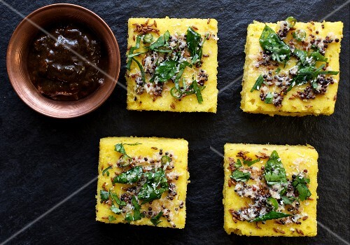 Dhokla (Indian chickpea cake) with mustard seeds, sesame seeds and a date and tamarind chutney