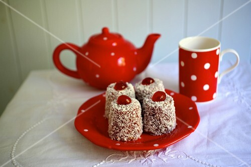 English Madeleines with raspberry jam and grated coconut with a teapot and a mug