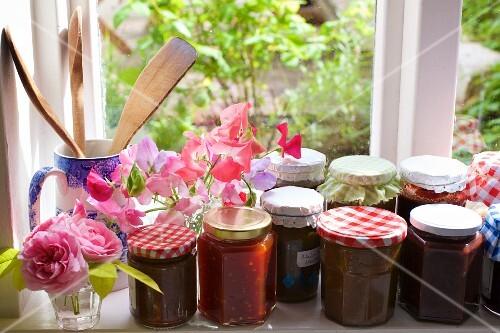 Various jars of jam on a windowsill