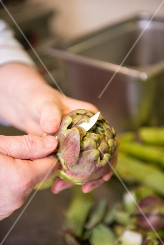 An artichoke being prepared