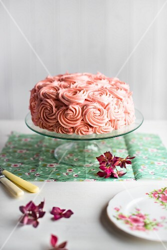 A festive pink cream cake on a cake stand